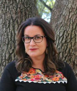 Author photo of Adrianna Cuevas standing against a tree trunk