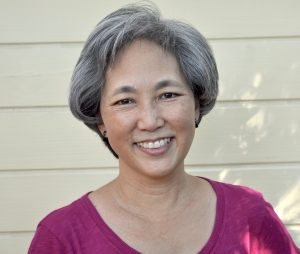 Author headshot of Carol Kim in a pink shirt against a background of beige siding