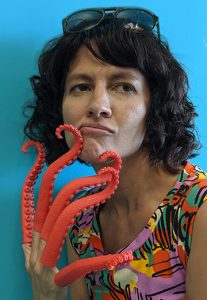 Author photo of Eliza Kinkz, with five red plastic squid-tentacles stuck on each finger of her right hand, one of which rests against her chin.
