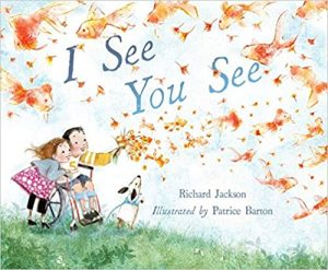 """Cover of """"I See You See,"""" featuring a boy in a wheelchair, a girl standing bent over next to him, and a dog on hind legs on a grassy hill looking together at a bouquet of orange flowers the boy holds that dissipate in the wind and form the shapes of goldfish"""