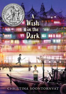 Cover of 'A Wish in the Dark': a boy on a boat in a canal holds out a glowing orb while a girl watches from a pier; multicolored glowing windows light up the buildings lining the canal. A Newbery sticker adorns the cover.