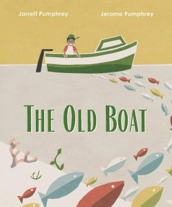 Cover of 'The Old Boat,' featuring a boy with a sideways cap smiling on a green and white fishing boat against a yellow sky; visible underneat in the grey water is a curving school of multicolored fish as well as plants and coral in a slope of underwater white sand.