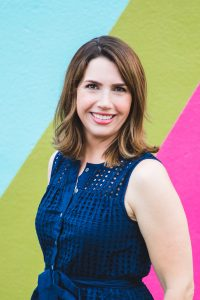 Author phot Kari Lavelle against blue, green, and pink striped background