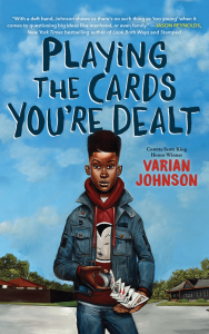 Cover of Varian Johnson's 'Playing the Cards You're Dealt,' featuring a Black boy in a red hoodie and jeans jacket deftly handling a pack of cards while standing on the street against a blue sky. Also features a blurb by Jason Reynolds.